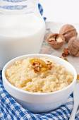 Porridge with nuts, raisins and jar of milk — Stock Photo