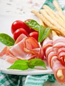 Grissini bread sticks with ham, tomato and basil — Stock Photo