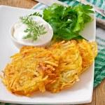 Potato pancakes with sour cream — Stock Photo #56209629