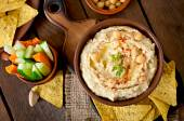 Hummus with vegetables, olive oil and pita chips — Stock Photo