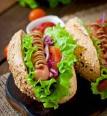 Hot dogs with sausages and vegetables — Stock Photo