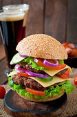Large burger with meat and vegetables and beer — Stock Photo