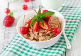 Oatmeal porridge with berries and glass of milk — Stock Photo