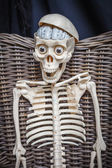 Skeleton sitting in a wicker chair — Stock Photo