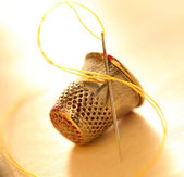 Sewing thimble and needle with thread — Stock Photo