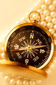Golden compass on pearl — Stock Photo