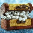 Wooden chest with white pearl necklace — Stock Photo #65788765