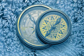 Vintage compasses on snowflakes — Stock Photo