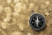 Black compass on soil background — Stock Photo