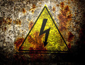 Old yellow high voltage sign — Stock Photo