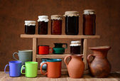 Various pottery and jam in jars of glass — Stock Photo