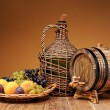 Wicker wine bottle, grapes and wooden barrel — Stock Photo #52374317