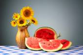 Sunflowers in a vase and sliced watermelon — Foto de Stock