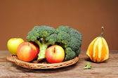 Broccoli, apples and decorative pumpkins — Stock Photo