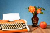 Typewriter apples and flowers in a vase — Stock Photo