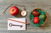 Easter eggs in a basket, apple and pocket watch — Stock Photo