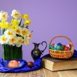 Coloured Easter eggs, books and flowers in a vase — Stock Photo #71547149