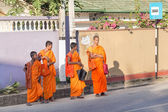 Group of buddhist monks in traditional orange robes waiting bus at station — Stock Photo