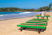 Local worker putting colourful wooden deck chairs on beach — Stock Photo
