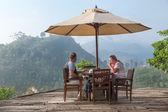 Tourist couple having breakfast at bungalow terrace — Stock Photo