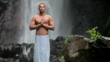 Man doing yoga under waterfall — Stock Video