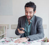 Man in restaurant looking on phone — Stock Photo