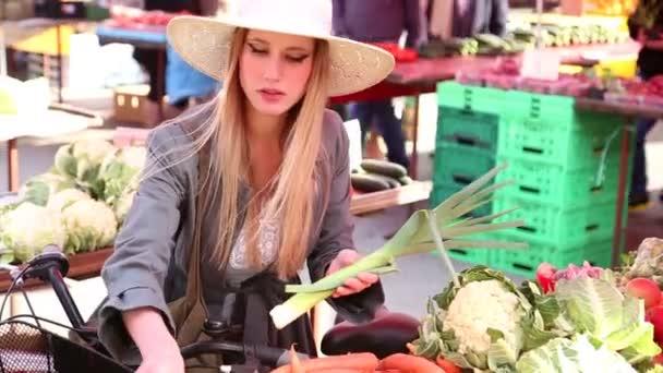 Puerros cosecha de chica en el mercado — Vídeo de stock