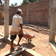 Local construction worker with wheelbarrow on building site. — Stock Video #57899061