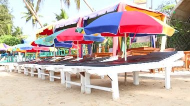 Sunbeds and parasols lined up on sandy beach — Stock Video