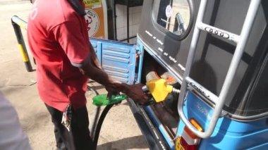 Local man putting petrol in tuktuk — Stock Video
