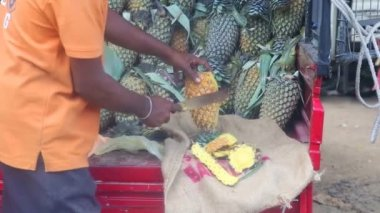 Local man slicing a pineapple at Hikkaduwa market. — Stockvideo