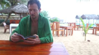 Man talking and reading a book in beach resort — Stock Video