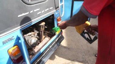 Local man putting petrol in tuktuk — Stockvideo
