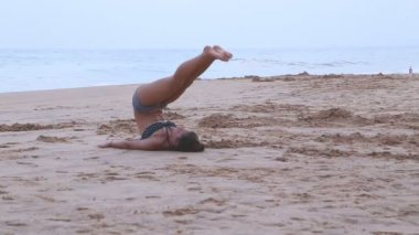 Woman stretching out on the beach — ストックビデオ