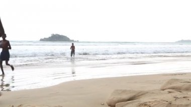 View of the ocean in Weligama with people enjoying the waves — Stock Video