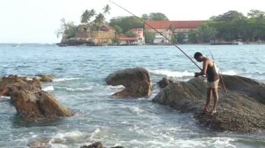 Fisherman fishing from a rock — Stock Video