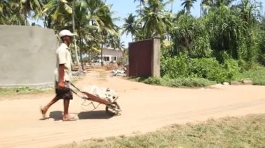 Local construction worker with wheelbarrow on building site. — Stock Video