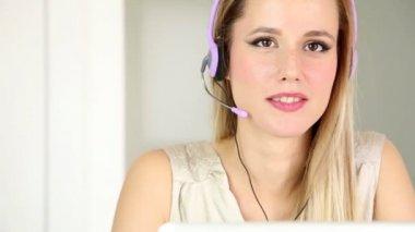 Mujer con auriculares en la computadora hablando con el cliente — Vídeo de Stock