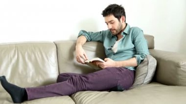 Man reading book in living room — Video Stock