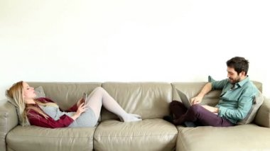 Couple speaking and using computers on couch — Vídeo de stock