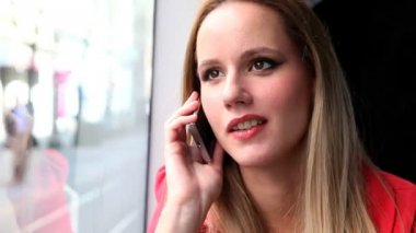 Beautiful blond woman sitting in tram and talking on phone — Stock Video
