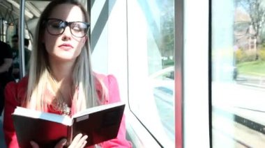 Woman sitting and reading in the tram — Stock Video