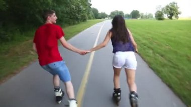 Woman and man rollerblading on a sunny day in park — Stockvideo