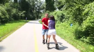 Woman and man rollerblading on a sunny day in park — Stock Video