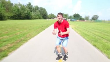 Young handsome man rollerblading in park — Stock Video