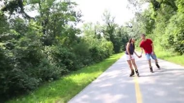 Woman and man rollerblading on a sunny day in park — Vídeo de Stock