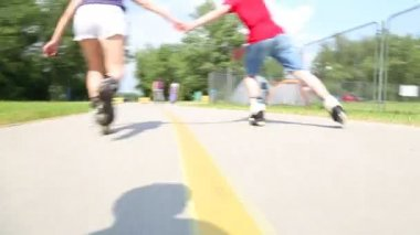 Young woman and man rollerblading — Stock Video