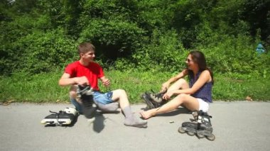 Young woman and man sitting on track, putting their rollerblades on their feet. — Wideo stockowe