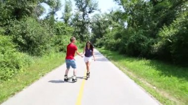 Woman and man rollerblading on a sunny day in park — ストックビデオ