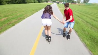 Young woman and man rollerblading and performing in park on a beautiful warm day, doing tricks — Stock Video